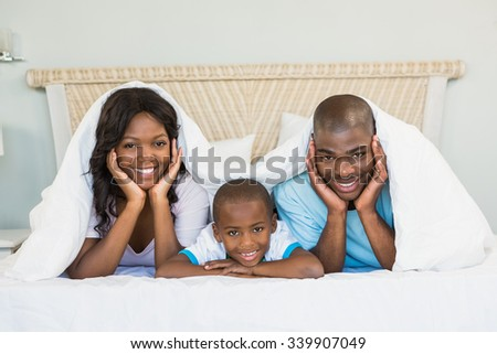 Happy family lying on bed at home - stock photo