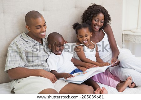 Happy family lying on bed reading book at home in the bedroom - stock photo