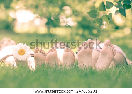 Happy family lying on green grass against blurred background. Children having fun outdoors in spring park. Retro toned image - stock photo
