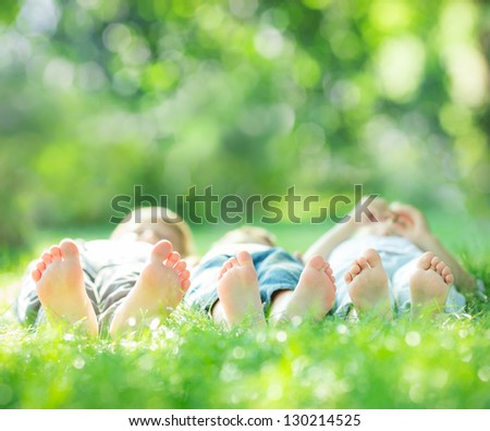 Happy family lying on green grass in spring park. Healthy lifestyle concept. Farmland vacations - stock photo