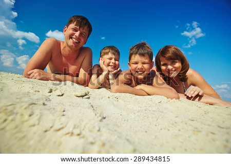Happy family lying on sandy beach and looking at camera - stock photo