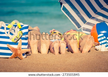 Happy family lying on the beach. Summer vacation concept - stock photo