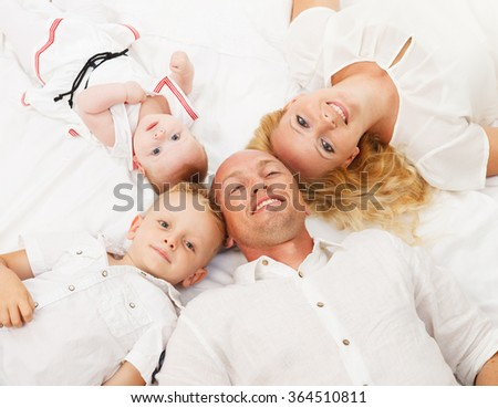 Happy family lying on the floor with heads together - stock photo