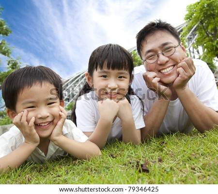 happy family lying on the grass.father with son and daughter - stock photo