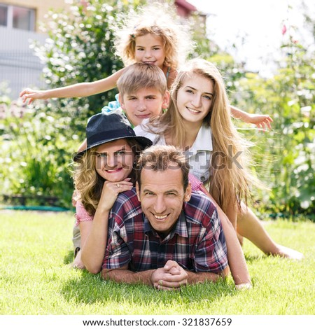 Happy family lying on the grass, having weekend in summer park - stock photo