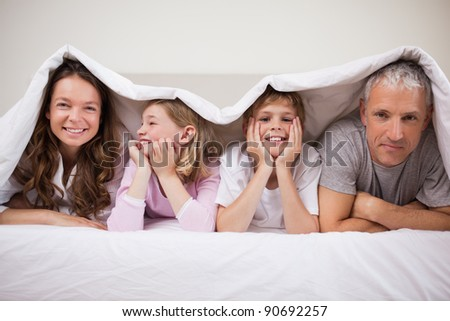 Happy family lying under a duvet in a bedroom - stock photo