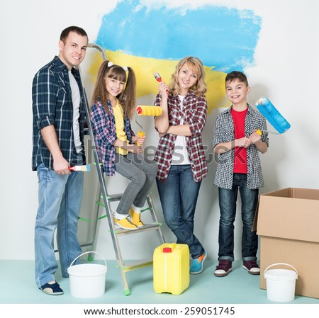 Happy family makes repairs at home. Smiling family painting big Ukrainian flag on wall at home - stock photo
