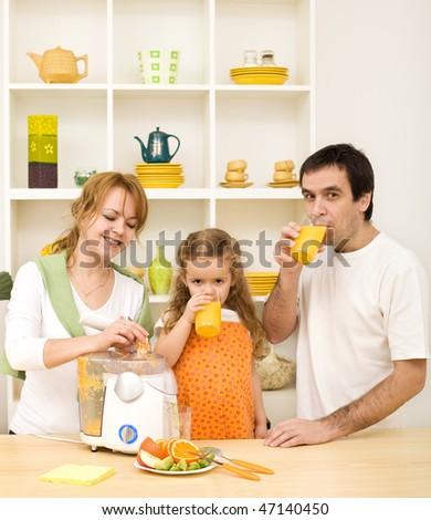 Happy family making fresh fruit juice and drinking - stock photo
