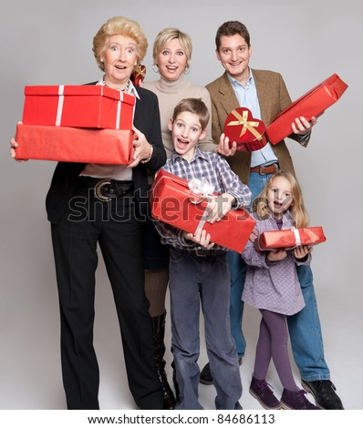 Happy family members holding gift boxes in different shapes