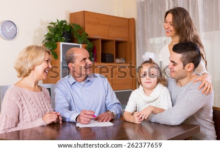 Happy family members ready to sign banking documents at home or office - stock photo