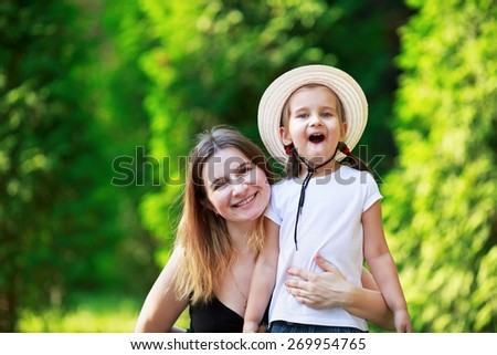 Happy family mom and baby little girl on the blurry background of fresh juicy summer greens. - stock photo