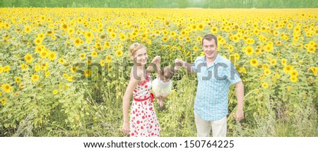 happy family - mom dad and daughter rocking her baby in her arms and having fun in the field of sunflowers. Father and mother watching something up in the sky. outdoor shot - stock photo