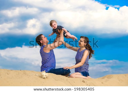 Happy family, mom, dad and little son in striped vests having fun  in the sand outdoors against blue sky background. Summer vacations concept.
