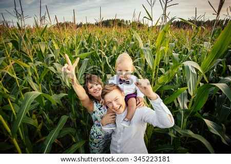 Happy family - mom, dad and son, standing in a large corn field in the Summer. - stock photo