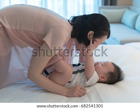 happy family. Mother and baby boy plays, hugging, kissing at home on the bed
