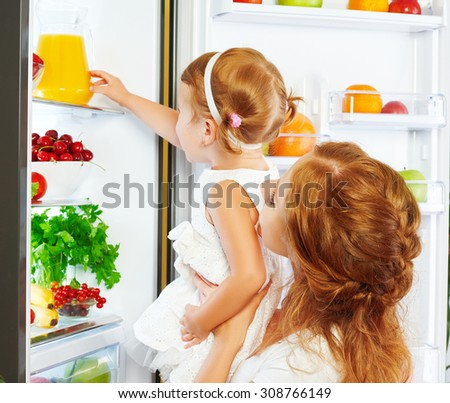 happy family mother and baby daughter drinking orange juice in the kitchen near the refrigerator - stock photo