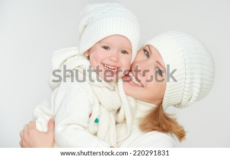 happy family: mother and baby daughter in white winter hats laughing on a gray background - stock photo