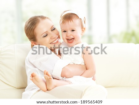 happy family. Mother and baby daughter plays, hugging, kissing at home on the sofa  - stock photo