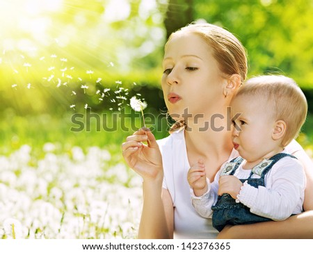happy family. Mother and baby girl blowing on a dandelion flower on the nature in the summer in the park - stock photo