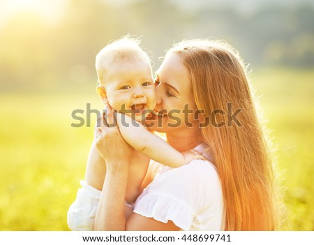 happy family mother and baby hugging and kiss in summer on the nature - stock photo