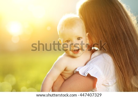 happy family mother and baby hugging in summer on the nature - stock photo