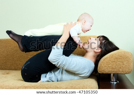 happy family: mother and baby on the sofa - playing and smiling - stock photo