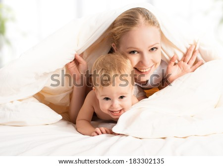 happy family mother and baby peeking out from under the blankets in bed - stock photo