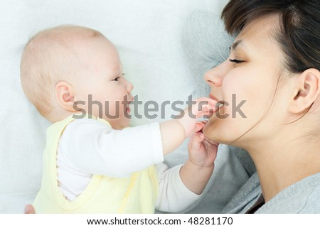 happy family: mother and baby - playing and smiling - stock photo