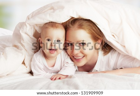 happy family. Mother and baby playing and smiling under a blanket - stock photo