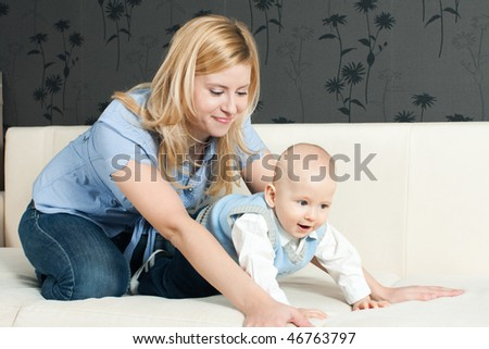 happy family: mother and baby sitting on the sofa and smiling - stock photo