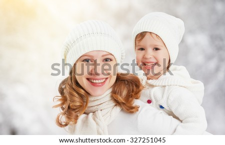 happy family mother and child baby daughter on a winter walk in the woods - stock photo