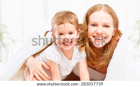 happy family mother and child baby daughter playing and having fun in bed - stock photo