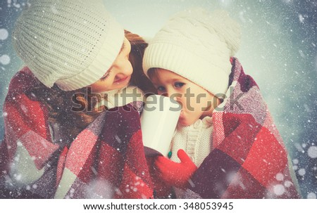 happy family mother and child daughter drinking hot tea on a winter walk outdoors - stock photo
