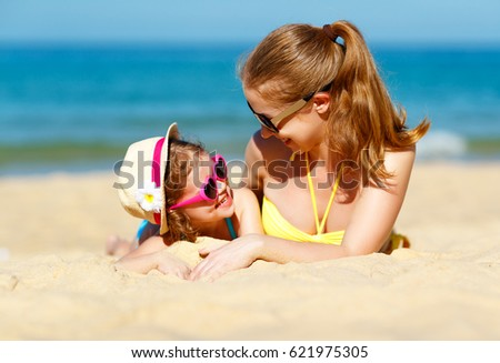 Happy family mother and child daughter  for swimming on beach in summer