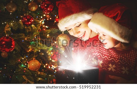 happy family mother and child daughter with magical gift from the Christmas tree