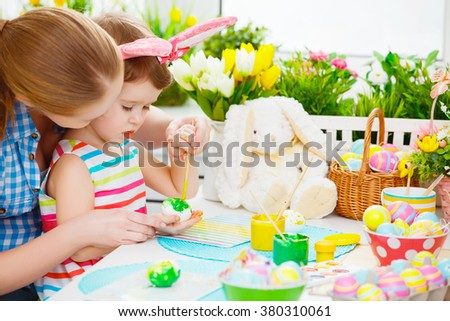 happy family mother and child girl paints eggs for Easter at home