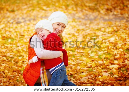 happy family: mother and child little daughter play, laughing cuddling on autumn walk in nature outdoors - stock photo
