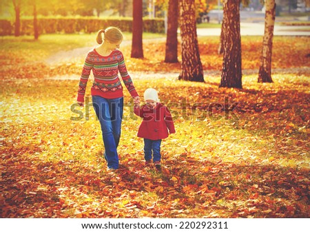 happy family mother and child little daughter running and playing on autumn walk - stock photo