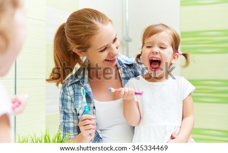 happy family mother and child little girl cleans teeth with a toothbrush in the bathroom - stock photo