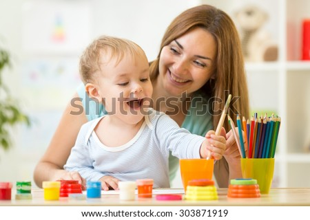 happy family mother and child painting together at home - stock photo