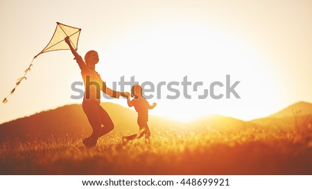 happy family mother and child run on meadow with a kite in the summer on the nature - stock photo