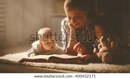 happy family mother and children read a book in the evening at home - stock photo