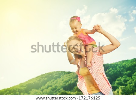 happy family. mother and daughter baby girl playing on nature outdoors - stock photo