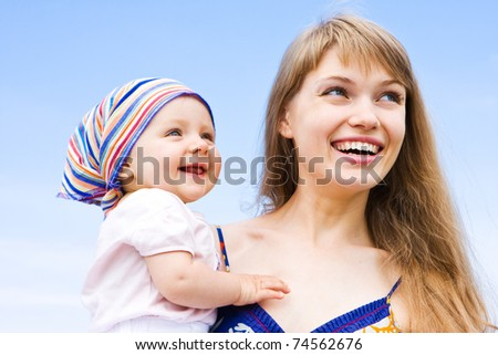 Happy family - mother and daughter. Blue skies on the background. - stock photo