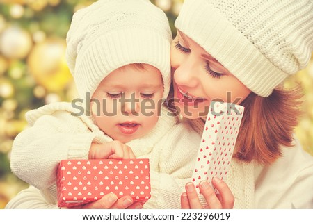 happy family mother and daughter in white hats with Christmas present in winter - stock photo
