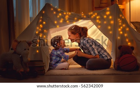 happy family mother and daughter playing at home in a tent
