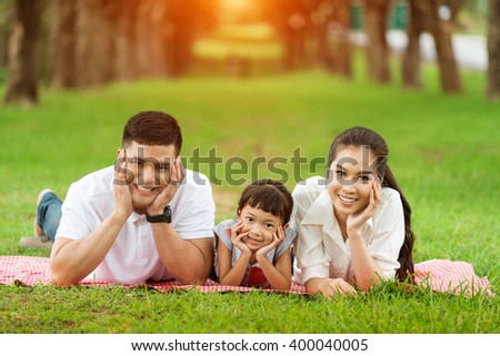 Happy family , mother and father in the park - stock photo
