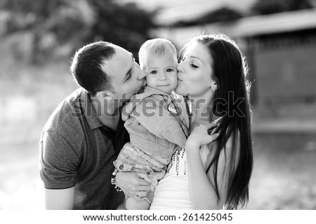 Happy family, mother and father kissing son, 1 year old, black and white, happy, love. Against the background of trees in a city park. - stock photo