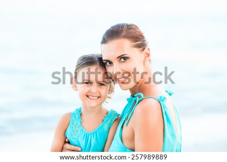Happy family mother and girl resting on the beach in beautiful turquoise azur dresses - stock photo