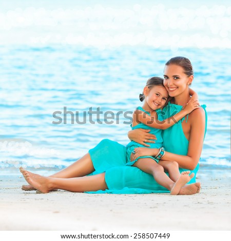 Happy family mother and girl resting on the beach in beautiful turquoise azure dresses - stock photo